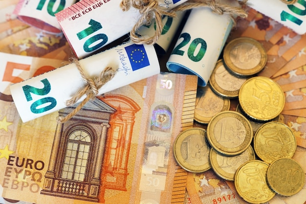 Veduta dall'alto di alcune banconote e monete arrotolate su più banconote Foto Gratuite
