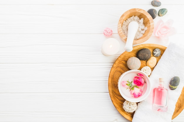 High angle view of spa stones; towel; flowers and oil on white background Free Photo