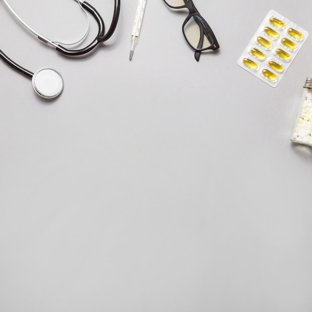 High angle view of spectacles; thermometer; stethoscope and pills on grey background Free Photo