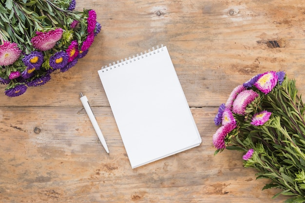 High angle view of spiral notepad; pen and bouquet of flowers on wooden desk Free Photo