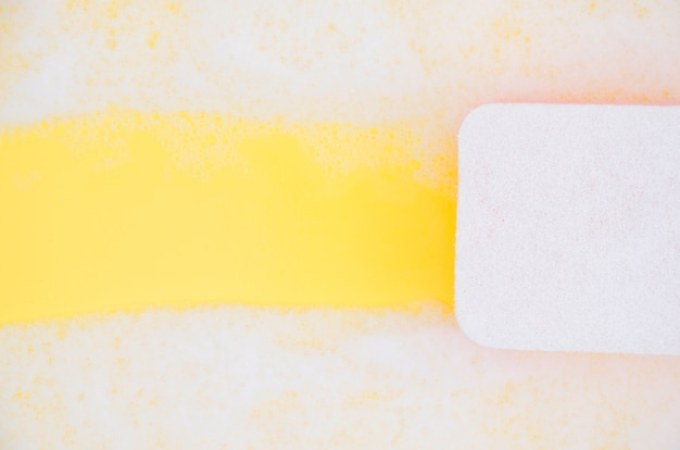 High angle view of sponge cleaning soap sud on yellow backdrop Free Photo