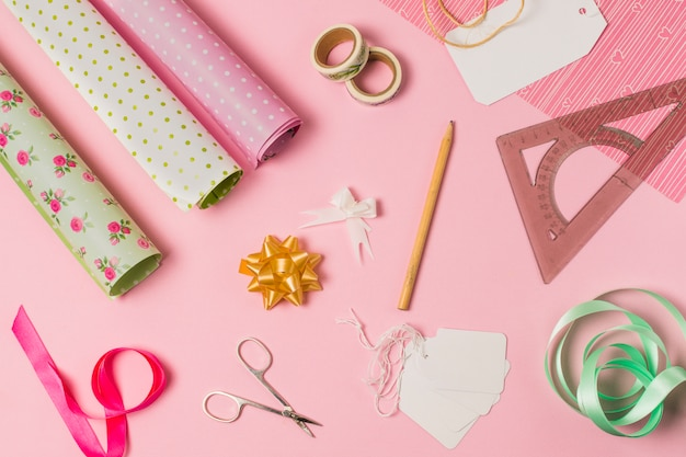 High angle view of stationery supplies with gift wrap and tags on pink background Free Photo