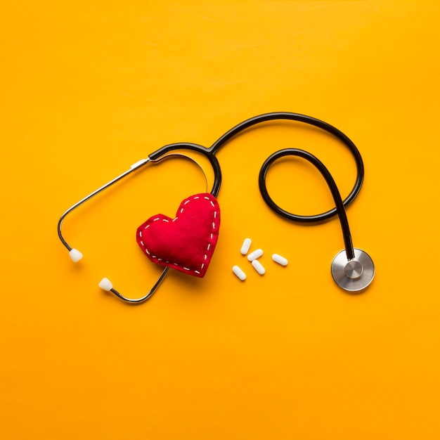 High angle view of stethoscope; stitched heart and medicines over yellow backdrop Free Photo