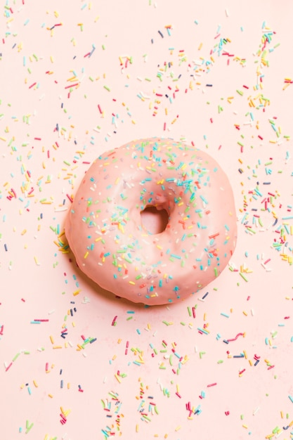 High angle view of sweet donut surrounded by colorful sprinkles Free Photo