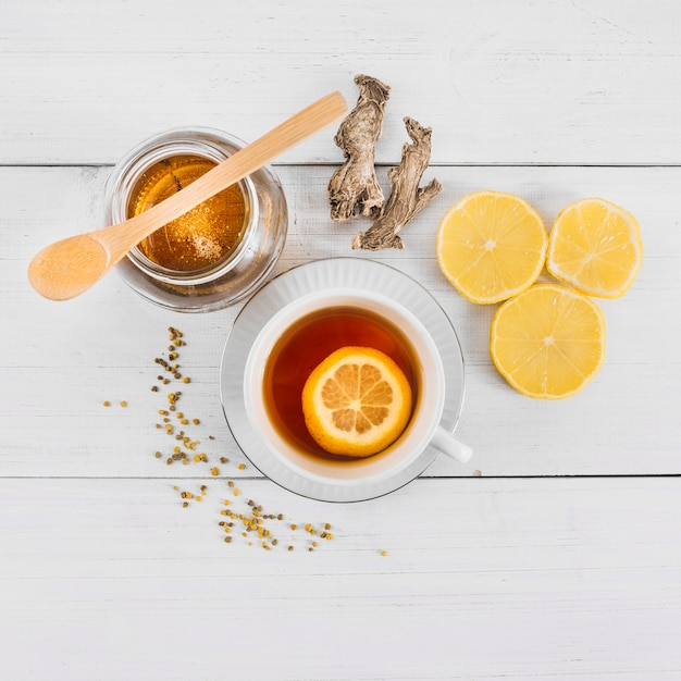 High angle view of sweet honey; lemon tea and ginger on wooden background Free Photo