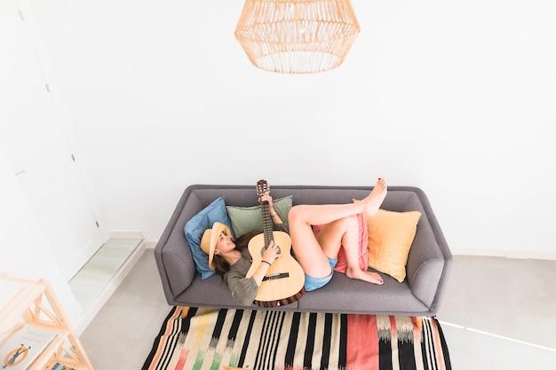 High angle view of a teenage girl lying on sofa playing guitar Free Photo