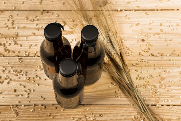 High angle view of three alcoholic bottles and ears of wheat on wooden surface Free Photo