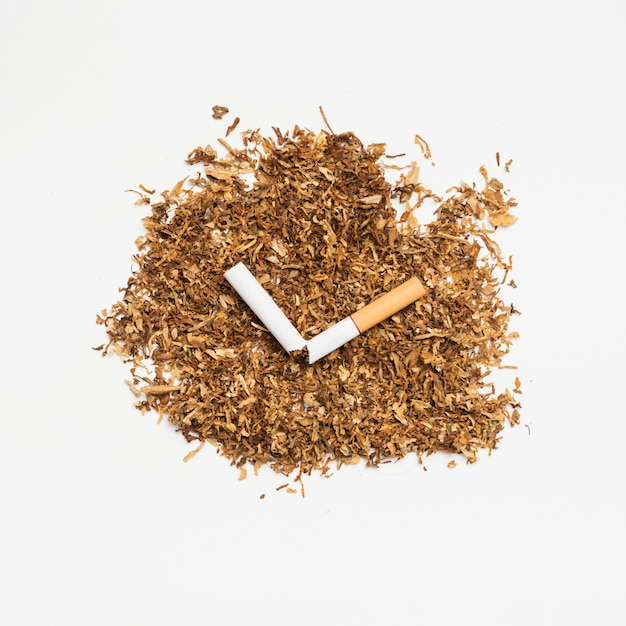 High angle view tobacco and broken cigarette over white surface Free Photo
