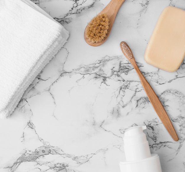 High angle view of towels; brush; soap and cosmetic bottle on marble surface Free Photo
