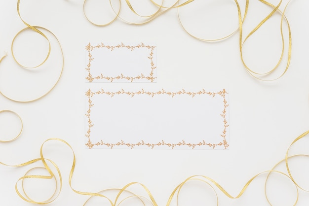 High angle view of two blank cards surrounded with ribbons on white surface Free Photo