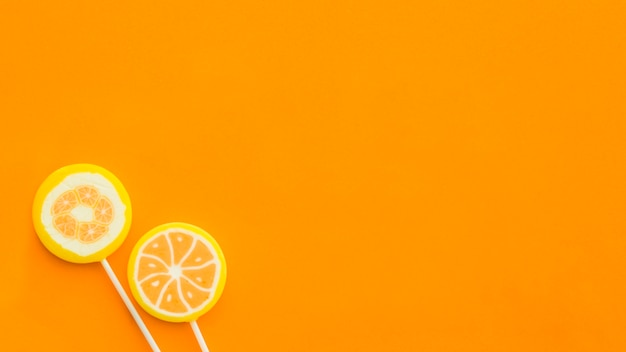 High angle view of two lollipops on orange surface Free Photo