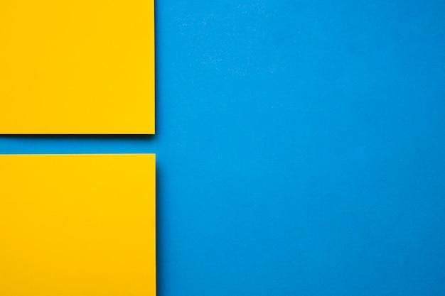 Un punto di vista dell'angolo alto di due carte gialle del cartone su fondo blu Foto Gratuite