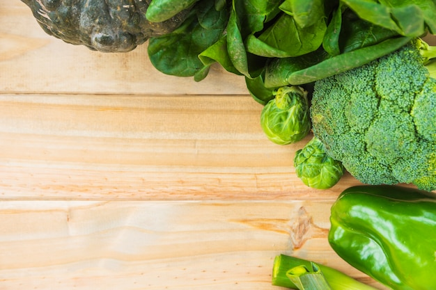 High angle view of various fresh green vegetables on wooden background Free Photo