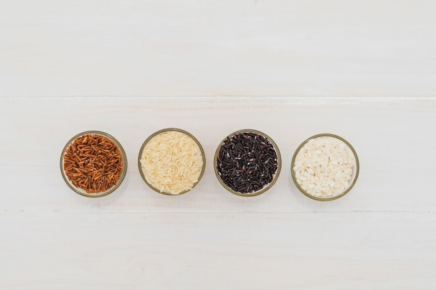 High angle view of various rice in bowls arranged in row over white table Free Photo
