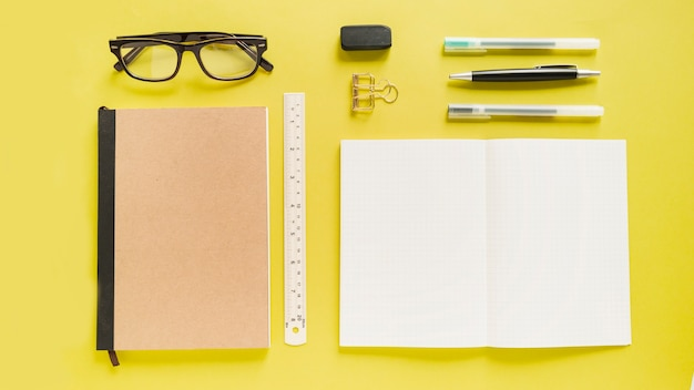 High angle view of various stationeries on yellow backdrop Free Photo