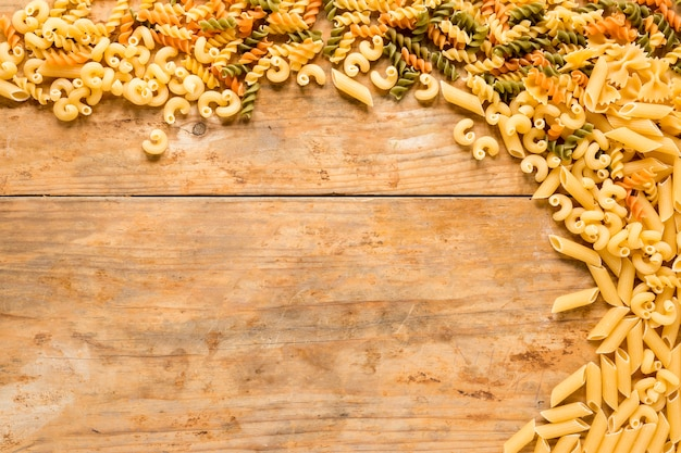 High angle view of various types of uncooked pasta on wooden desk Free Photo