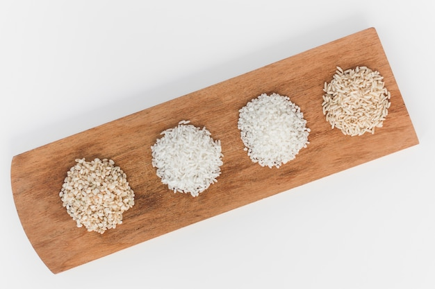 High angle view of various uncooked rice on wooden tray Free Photo