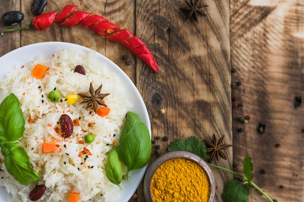 High angle view of vegetable rice; turmeric powder; red chili pepper and dry spices over wooden backdrop Free Photo