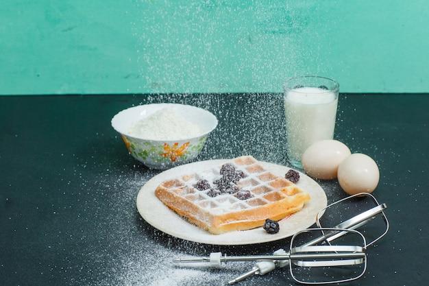 暗い、シアンの卵、小麦粉、牛乳、ミキサー棒でプレートの高角度のビューワッフル。横型 無料写真