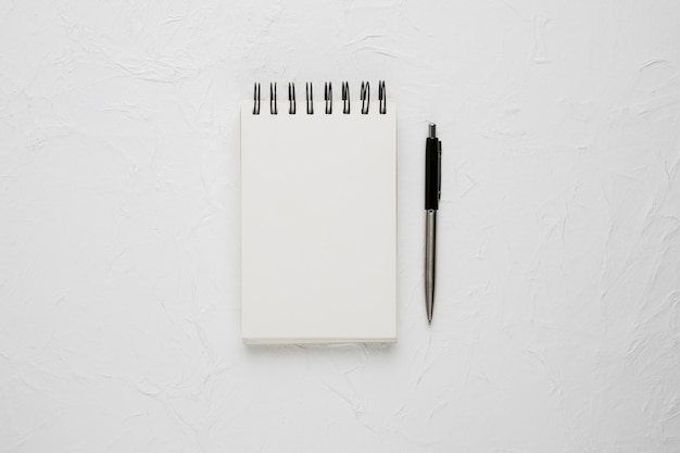 High angle view of a white blank spiral notepad with ballpoint pen Free Photo