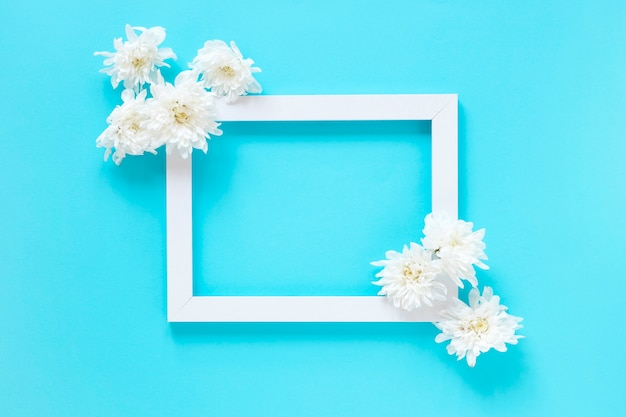 High angle view of white flowers and blank picture frame on blue background Free Photo