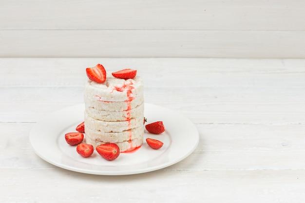흰색 나무 보드 표면에 딸기와 접시에 높은 각도보기 흰 쌀 케이크. 무료 사진