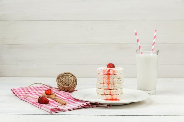 Wafer di riso bianco vista dall'alto sul piatto con fragole, meringhe, bugna di corda e latte sulla superficie del bordo di legno bianco. Foto Gratuite