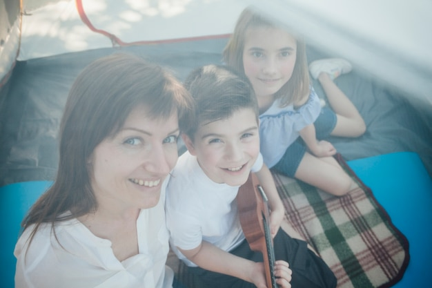 High angle view of woman and her children sitting in tent Free Photo