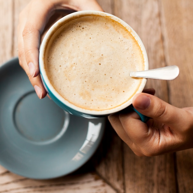 High angle view of woman's hand holding coffee cup with frothy foam Free Photo