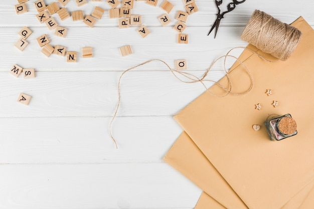 High angle view of wooden text cube; string spool scissor with brown paper on white table Free Photo