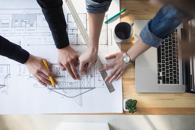 High angle view of worker's hand working on blueprint over wooden table at workplace Free Photo