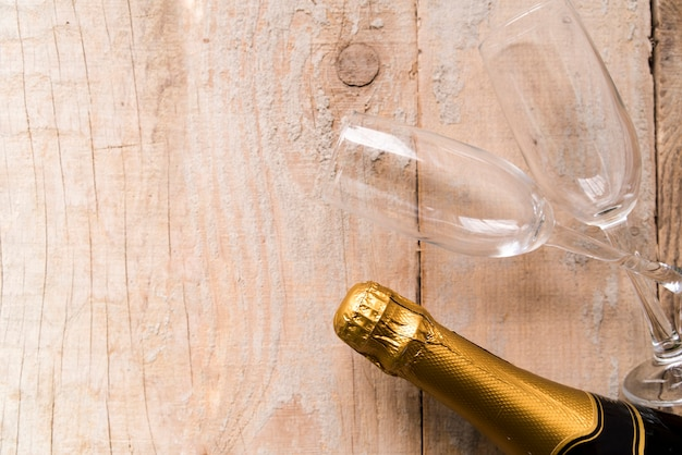 High angle view of wrap champagne bottle and empty glasses on wooden surface Free Photo