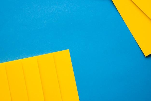 Vista dell'angolo alto delle carte del cartone giallo sul contesto blu Foto Gratuite
