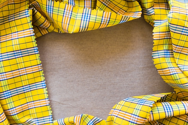 High angle view of yellow chequered pattern table cloth forming frame Free Photo