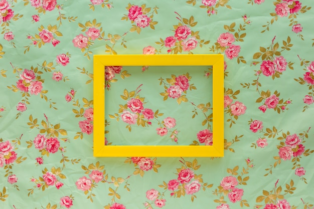 High angle view of yellow empty frame against floral print background Free Photo