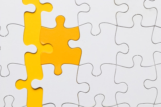High angle view of yellow puzzle piece arranged with white pieces Free Photo