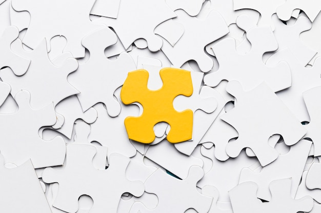 High angle view of yellow puzzle piece over white puzzle pieces Free Photo