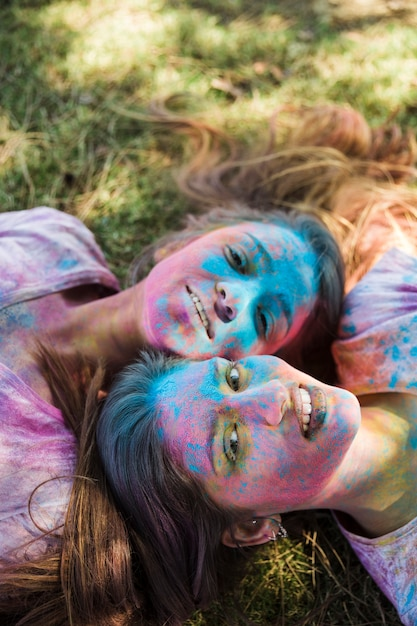 High angle view of young women with holi color on their face lying on lawn looking at camera Free Photo