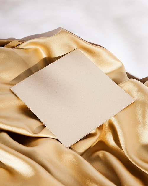 High angle white card on golden cloth Free Photo