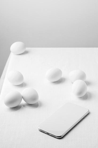 Белые куриные яйца под высоким углом на столе с телефоном Бесплатные Фотографии