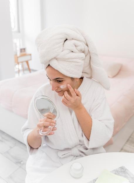 Donna ad alto angolo che applica crema per il viso Foto Gratuite