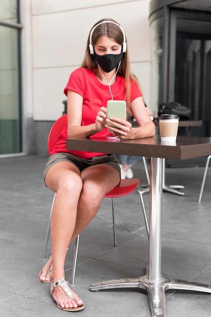 マスク付きのテラスでハイアングルの女性 無料写真