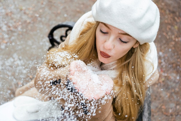 High angle of woman blowing snow at the park in winter Free Photo