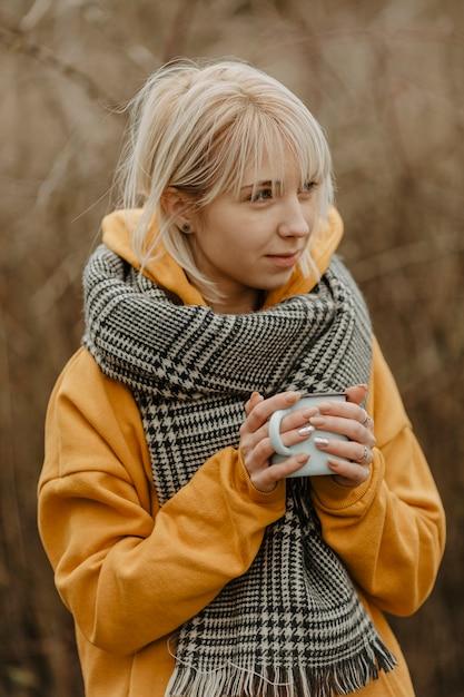 High angle woman drinking tea to warm up Free Photo