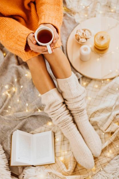 Donna di alto angolo che gode delle vacanze invernali con una tazza di tè Foto Gratuite