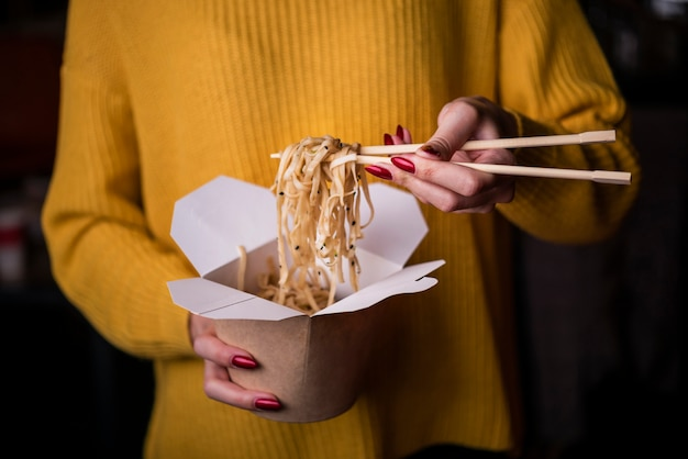 High angle of woman holding box of noodles Free Photo