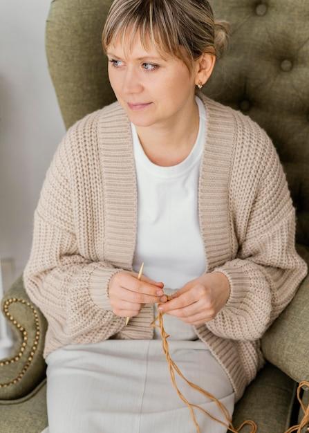 Donna di alto angolo che lavora a maglia all'interno Foto Gratuite