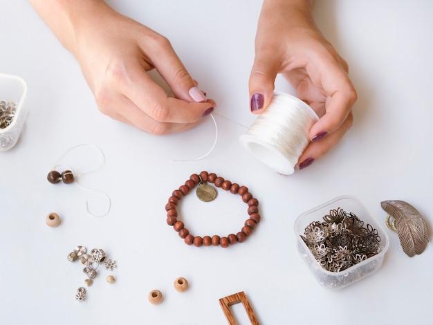 High angle of woman making a bracelet Free Photo