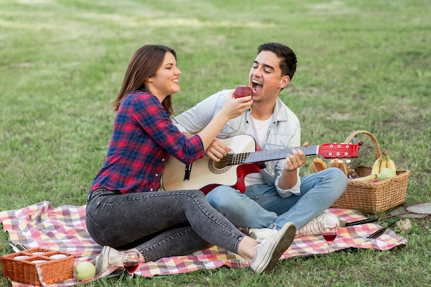 High angle woman offering an apple to man Free Photo
