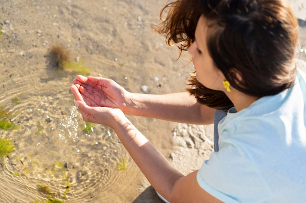 High angle of woman reaching for water outdoors Free Photo